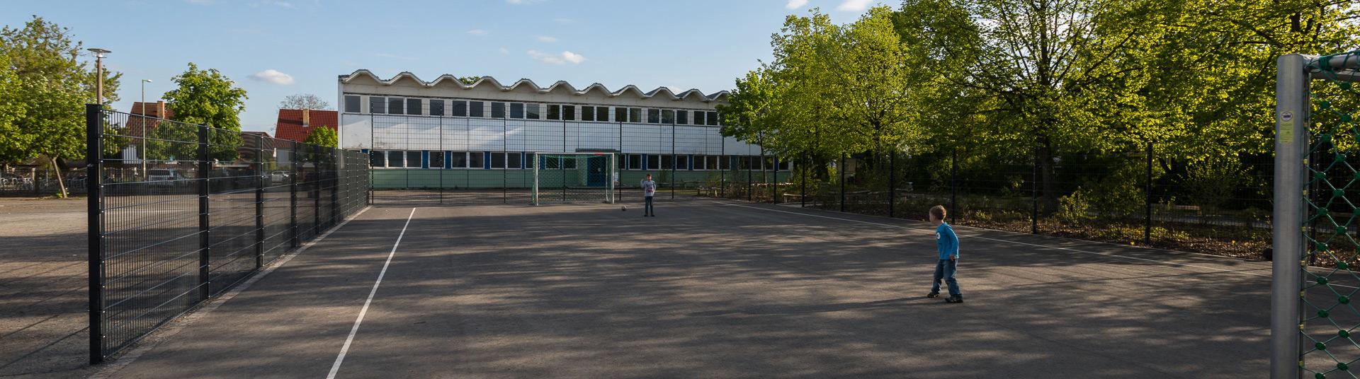 Fußballplatz mit zwei spielenden Kindern